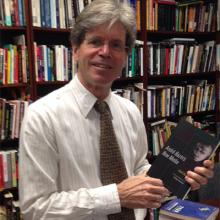 Professor Dudley Andrew holding his new publication, a collection of Andre Bazin's essays